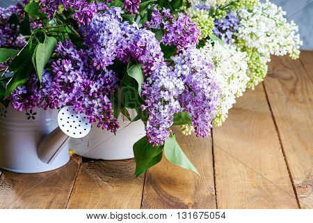 Purple and white lilac bunch with watering can