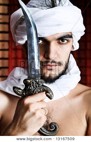 Shot of a man in oriental costume holding daggers.