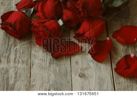 bouquet withered red roses and petals lying on a wooden table