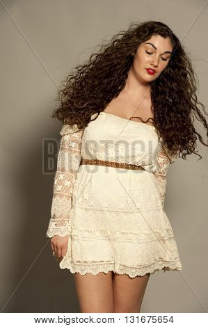 Beautiful young female brunette with curly hair in a studio setting while wearing a white dress on a gray background.