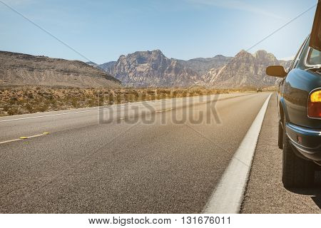 Road in Southern Nevada with car on the side of road