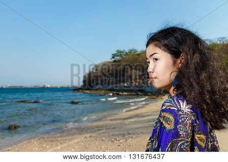 asian woman long black hair with blue shawl and white jeans on sea and blue sky blur background