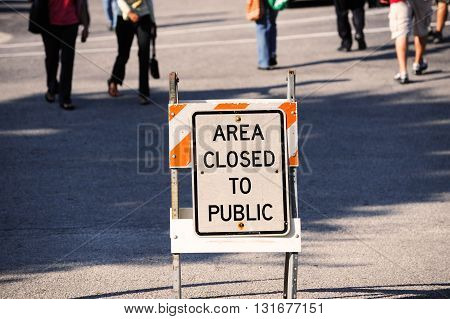 area closed sign and people behind, urban street scene