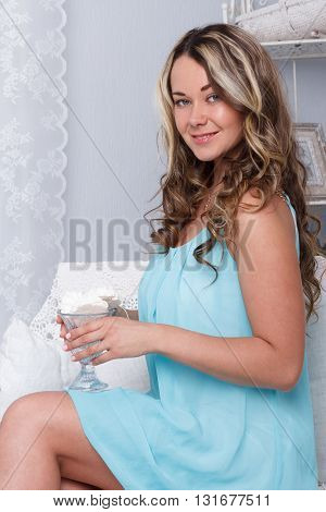 Pretty young woman sitting on vintage retro white sofa couch