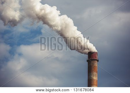 Smoke rising from an industrial chimney, clouds for background