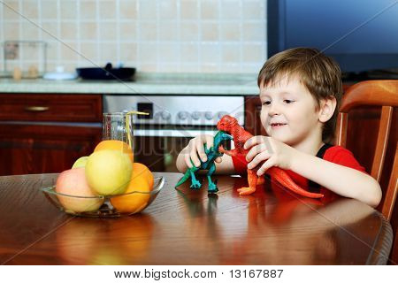 Little boy is playing with his toys at home.