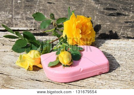 Soap and yellow rose on wooden background
