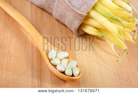 Seeds of beans on wooden spoon and heap of beans in jute bag lying on wooden table healthy food and nutrition