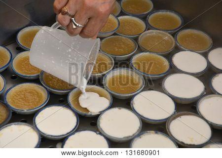 process of making coconut milk custard in small porcelain cup (Thai dessert).
