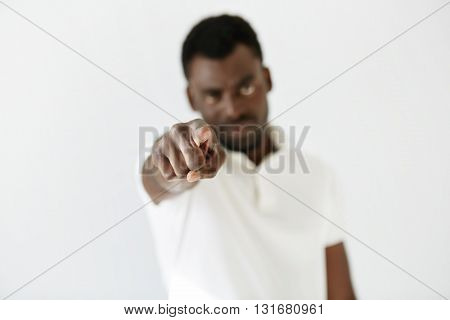 Headshot Of African American Man Pointing A Finger Right At The Camera. Young Black Male Wearing Whi