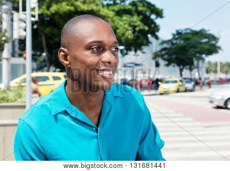 Laughing african american man in bright shirt looking sideways outdoor in the city in the summer