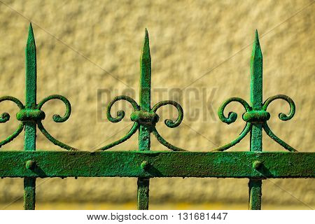 Old fence rusty forged metallized with peeled green paint on sunny day on yellow wall background