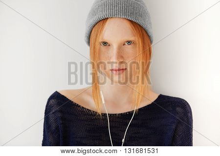 Portrait Of Teenager With Ginger Hair Wearing Hipster Cap Listening To Her Favorite Music With Headp