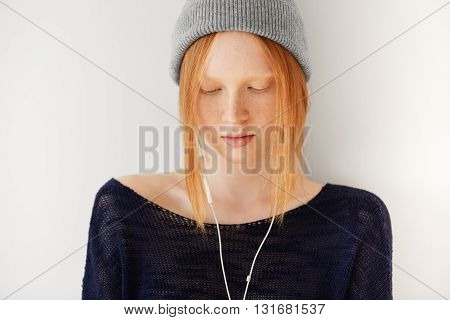 Cute Student Girl With Ginger Hair And Freckles Wearing Gray Hipster Cap Looking Down While Listenin