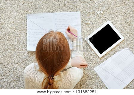 Overhead View Of Hardworking Redhead Teenager Lying On The Floor, Making Notes In Copybook, Using Di