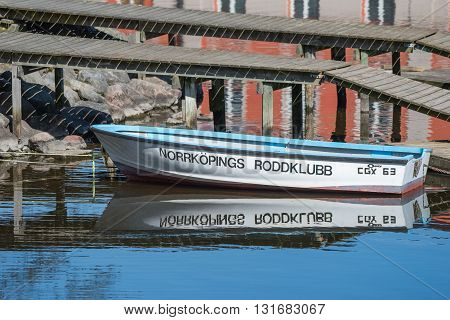 NORRKOPING, SWEDEN - MAY 6, 2016: Rowing boat moored at Stromsholmen island in Motala river, Norrkoping. Norrkoping is a historic industrial town in Sweden.