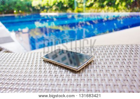 Smartphone put on armchair beside the pool means to get resting away from business