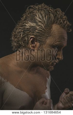 Strong, covered with mud all over her naked body on black background man. adventure and risk, competition force
