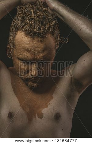 Strength, covered with mud all over her naked body on black background man. adventure and risk, competition force