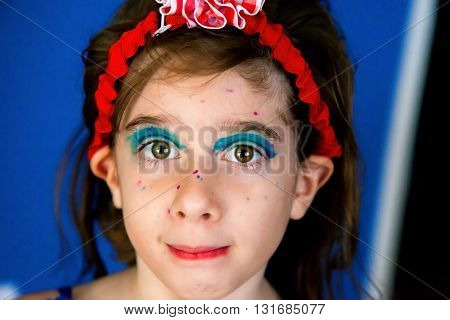 A young girl who gave herself a magic marker makeover looks confidently at the camera.