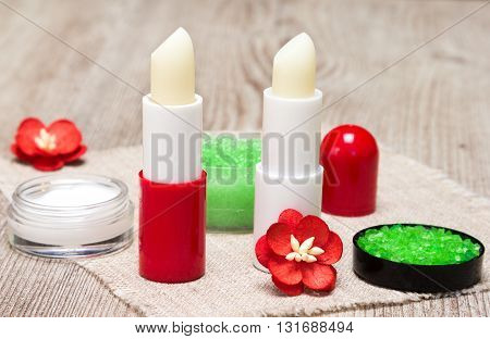 Cosmetics for lip skin care: close-up of sea salt, natural honey scrub with essential oils, lip cream and balms with flowers on shabby wooden surface and sackcloth napkin