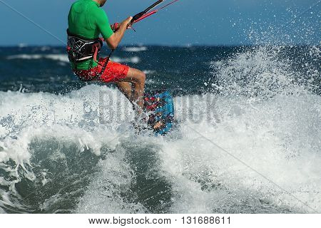 Kitesurfer overcome big wave in the ocean back view