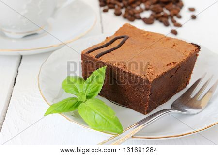 a piece of chocolate cake and coffee beans; shallow depth of field