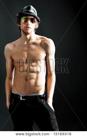 Retrato de um jovem musculoso bonito. Filmado em um estúdio.