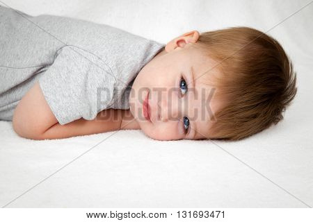 A handsome little boy laying on his stomach with head down on a white background smiles sweetly at the camera.