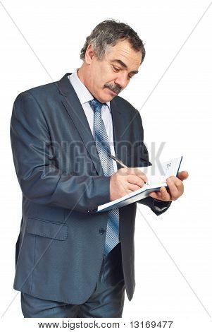 Smiling Mature Executive Taking Notes In Agenda