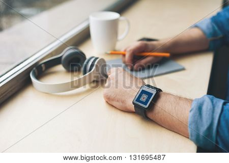 Close up of hands of young man sitting at the windowsill near a cup and headphones. He is holding a pencil under the writing-pad. Focus on his smart watch