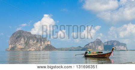 Seascape with limestone mountain and wooden long-tail boat at Pak Meng Beach in Trang province Thailand