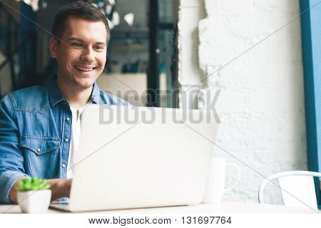 Cheerful guy is working on a laptop. He is sitting at table in cafe and smiling