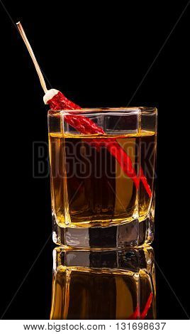 A glass of vodka and red chili peppers isolated on a black background.
