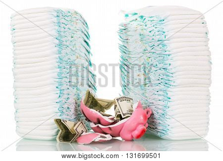Stacks of children's disposable diapers, broken piggy bank and money isolated on white background.