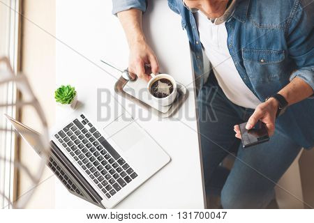 Top view of cheerful guy holding a mobile phone and messaging. He is drinking a cup of coffee with enjoyment. Guy is sitting at desk near a laptop