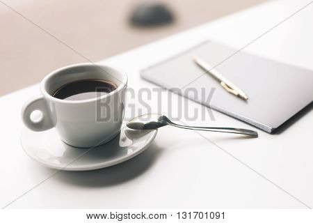 Close up of mug of coffee with writing-pad on desk