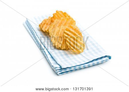 Crinkle cut potato chips isolated on white background. Tasty spicy potato chips on checkered napkin.