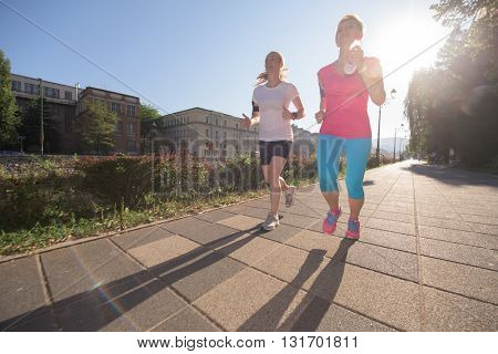 two middle aged female friends jogging have morning workout with sunrise in background