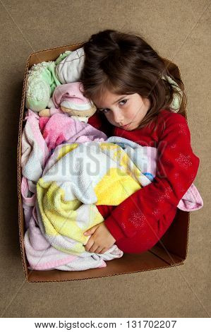 A young girl with a fever rash curls up in a box to cuddle with her blanket an stuffed animals.