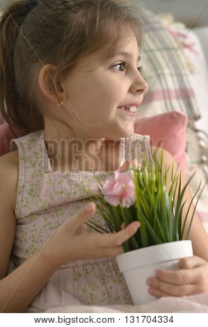 Beautiful little girl posing with  flowers at home.