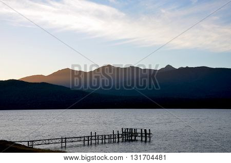 Wispy clouds above mountains and lake at dusk