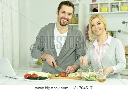 happy couple cooking in  kitchen at home with laptop