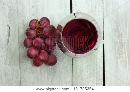 A photo of a glass of red wine with a bunch of grapes shot from above on a light blue wooden background texture enriched by a layer of watercolor with copyspace