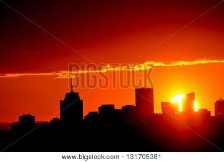Glowing orange sun setting behind city buildings in silhouette