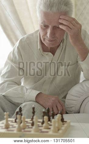 Portrait of a serious senior man playing chess