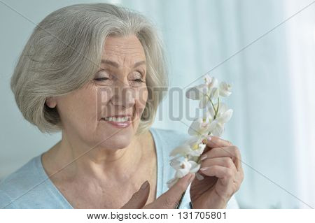 Senior woman portrait with blooming orchid flowers