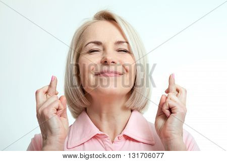 Closeup portrait hopeful beautiful woman crossing her fingers eyes closed hoping asking best isolated on white wall background. Human face expression emotions feeling attitude reaction