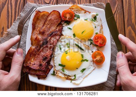Man Eating His Breakfast Of Scrambled Eggs, Bacon And Tomato