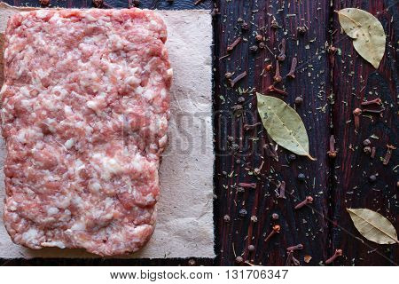 Minced Meat On A Black Background, Sprinkled With Spices And Bay Leaves Space For Text